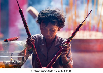 HO CHI MINH CITY, VIETNAM - FEBRUARY 6, 2005: Senior woman shrouded in incense smoke, places two offerings into an urn within the Thien Hau Temple in Chinatown, Ho Chi Minh City.