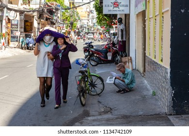 HO CHI MINH CITY, VIETNAM - NOVEMBER 20: Vietnamese women hide from the sun on Bui Vien Street in Ho Chi Minh City on November 20, 2015 in Ho Chi Minh City, Vietnam.