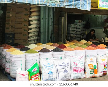 HO CHI MINH CITY, VIETNAM - DECEMBER 14, 2013: female vendor with sacks of legumes and grains in Vietnamese street market