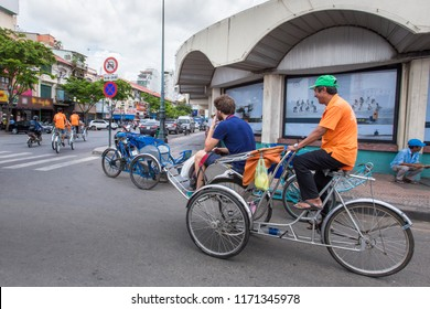 """Ho Chi Minh City, Vietnam - September 1, 2018: Vietnamese undefined cyclists are taking the guests to the downtown. The cyclists in orange t-shirts with the phrase """"Vietnamese Cyclos"""""""