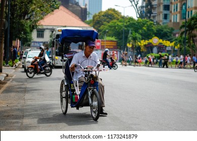 Ho Chi Minh city, Vietnam - JUL 2018: Disabled man on the wheel chair sells the lottery. Royalty high quality free stock photo of a man sit the wheelchair and sell government's lottery at a street mar