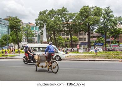 Ho Chi Minh City, Vietnam - September 12, 2018: Unidentified man riding a traditional cyclo in Saigon Notre-Dame Cathedral Basilica, Vietnam.