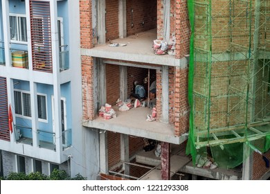Ho Chi Minh City / Vietnam 11 02 2018: Workers are setting the electricty up in the wall of a bricks building.