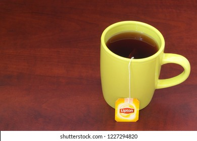HO CHI MINH CITY, VIETNAM - NOVEMBER 11, 2018: Lipton tea in yellow cup with tea bag on wooden table. Lipton is one of the famous brands in tea industry.