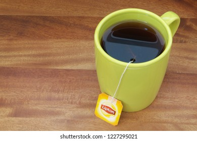 HO CHI MINH CITY, VIETNAM - NOVEMBER 11, 2018: Lipton tea in cup with tea bag on wooden table. Lipton is one of the famous brands in tea industry.