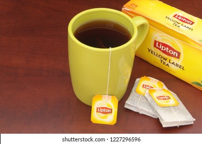 HO CHI MINH CITY, VIETNAM - NOVEMBER 11, 2018: Lipton tea in yellow cup and tea bags and box on wooden table. Lipton is one of the famous brands in tea industry.