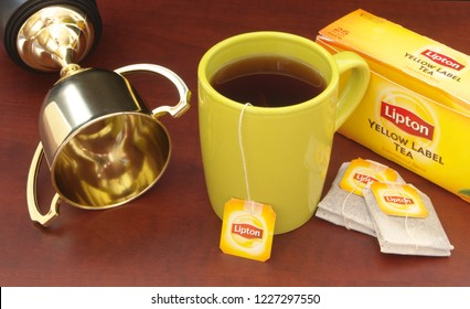 HO CHI MINH CITY, VIETNAM - NOVEMBER 11, 2018: Lipton tea in cup and tea bags with golden cup on wooden table. Lipton is one of the famous brands in tea industry.