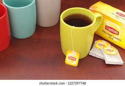HO CHI MINH CITY, VIETNAM - NOVEMBER 11, 2018: Lipton tea in cup and tea bags and box on wooden table. Lipton is one of the famous brands in tea industry.