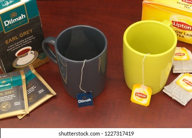 HO CHI MINH CITY, VIETNAM - NOVEMBER 11, 2018: Lipton abd Dilmah tea bags in cups and boxes of tea on wooden table. Lipton and Dilmah are  famous brands in tea industry.