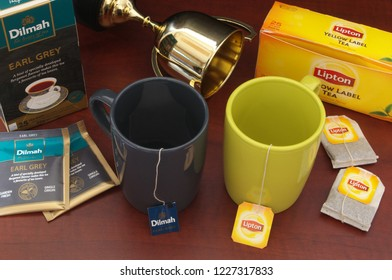 HO CHI MINH CITY, VIETNAM - NOVEMBER 11, 2018: Lipton abd Dilmah tea bags in cups, boxes of tea and champion cup on wooden table. Lipton and Dilmah are  famous brands in tea industry.