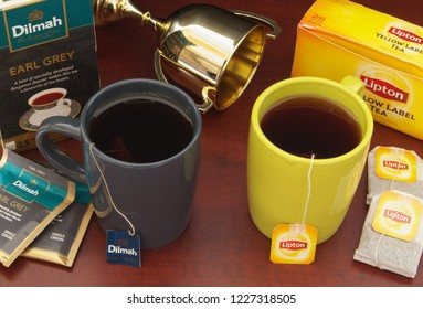 HO CHI MINH CITY, VIETNAM - NOVEMBER 11, 2018: Lipton and Dilmah tea in cups, tea bags with boxes of tea with golden cup on wooden table. Lipton and Dilmah are  famous brands in tea industry.