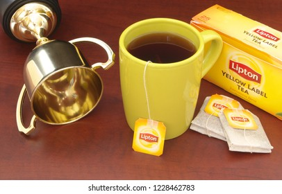 HO CHI MINH CITY, VIETNAM - NOVEMBER 11, 2018: Lipton tea in cup and tea bags with champion cup on wooden table. Lipton is one of the famous brands in tea industry.