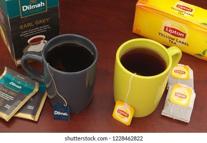 HO CHI MINH CITY, VIETNAM - NOVEMBER 11, 2018: Lipton and Dilmah tea in cups and tea bags with boxes of tea on wooden table. Lipton and Dilmah are  famous brands in tea industry.
