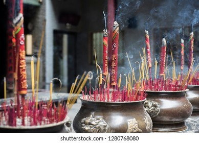 Ho Chi Minh City / Vietnam 17 Dec. 2018: Large and red incense sticks with Chinese caracters on them in bronze pots burn in a Buddhist temple.