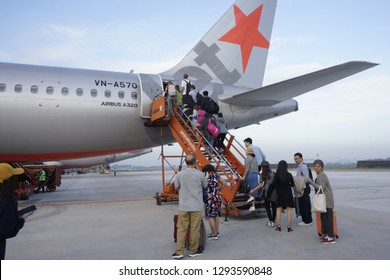 Ho Chi Minh City / Vietnam - Dec 17, 2018: A Jetstar flight to Dalat City in early morning. The airline is one of the low cost carriers in Vietnam. Passengers are brought to the plane by shuttle bus.