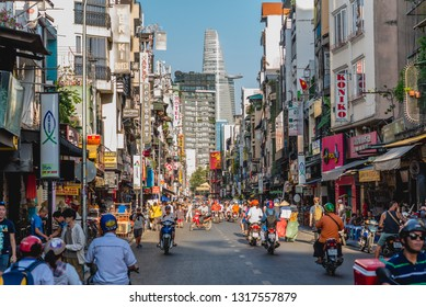 Ho Chi Minh City, Vietnam - January 7, 2019: Bui Vien Street crowded with people and road traffic with numerous signboards of hotels & restaurants and Bitexco Financial Tower at the end of perspective