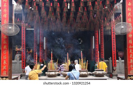 HO CHI MINH CITY, VIETNAM - JANUARY 5. 2015: Inside Buddhist temple with hanging spiral incense coils and burning sticks with massive smoke