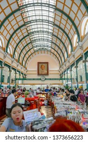 Ho Chi Minh City, Vietnam - March 8, 2019 :  Tourists buying souviniers inside old General Post Office under portrait of Ho Chi Minh in Saigon, Vietnam.