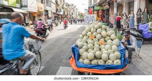 Ho Chi Minh City, Vietnam - April 27, 2019: a cart of melons, a row of mannequins and dragon costumes for sale next to the road traffic in Tran Hung Dao Street, Cho Lon (Saigon's Chinatown).
