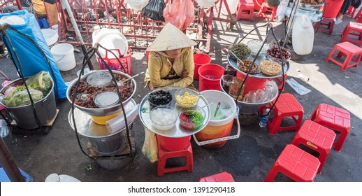 Ho Chi Minh City, Vietnam - April 15, 2019: a vendor sits by plates with ingredients for sam bo luong, a cold sweet soup (dish of Chinese origin) at Cho Binh Tay market in Cho Lon, Saigon's Chinatown.