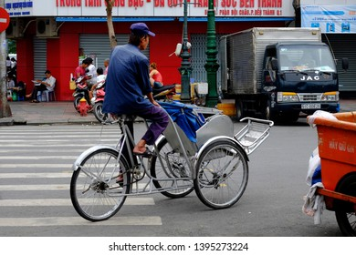 HO CHI MINH CITY, VIETNAM - SEPTEMBER 28, 2014: Vietnamese man riding bicycle to pick up tourists in Ho Chi Minh City.
