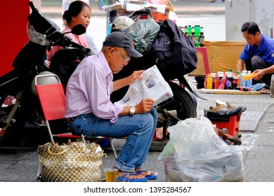 HO CHI MINH CITY, VIETNAM - SEPTEMBER 28, 2014: Vietnamese old man reading newspaper by the roadside in Ho Chi Minh City.