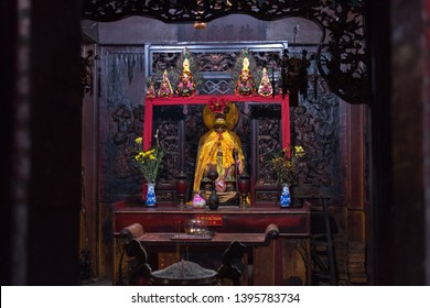 Ho Chi Minh City, Vietnam - April 27, 2019: one of the altars of Ha Chuong Hoi Quan pagoda with statue of Hanuman and wooden carving depicting army of monkeys. The temple located in Cho Lon, Chinatown