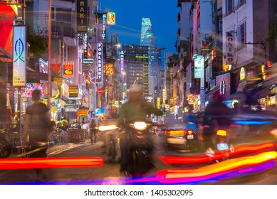 Ho Chi Minh City, Vietnam - April 22, 2019: famous Bui Vien Street at night with its neon lights, silhouettes, colorful lines of headlights, and Bitexco Tower in the background. Long exposure.