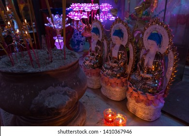 Ho Chi Minh City, Vietnam - April 27, 2019: a closeup of the obscure temple interior with incense sticks, candles, statues lit with purple lamp light in Tam Son Pagoda, Cho Lon (Saigon's Chinatown).