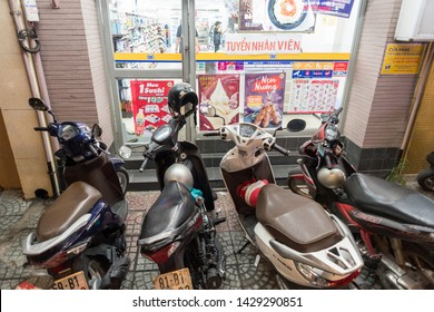 Ho Chi Minh City, Vietnam - May 3, 2019: inconveniently parked motorbikes block the entrance door of a convenience store. Inconvenience and unsafety in the streets is a part of experience in Vietnam.
