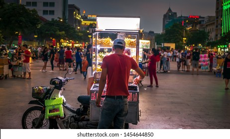 Ho Chi Minh City / Vietnam - July 13th 2019: A street food vendor with a portable stall selling various types of fish ball, chicken ball and beef ball skewers on a motorbike, Saigon, Vietnam.