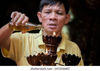 Ho Chi Minh City / Vietnam - July 7 2019: Monk adding oil to torches as a religios gift at Chùa Ngọc Hoàng temple in Saigon, vietnam