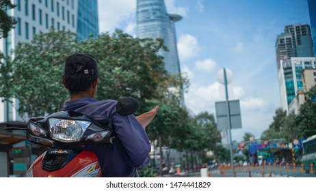 Ho Chi Minh city, Vietnam - AUGUST 1, 2019 : A guy chills on the motorbike with a Bitexco building in the background