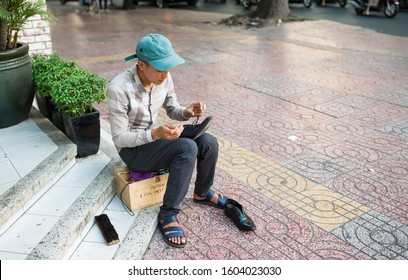 Ho Chi Minh city, Vietnam. April 18, 2017. A shoeshine boy sits on the steps of the mall.