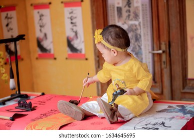 Ho Chi Minh city, Vietnam - January  5th 2020: Cute baby girl wearing a yellow dress for Tet holidays
