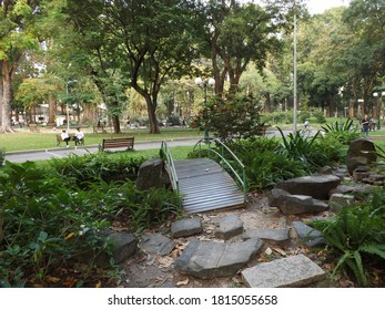 Ho Chi Minh City / Vietnam - November 18 2019: a small bridge in a city park, with people relaxing around the park and on the park benches.