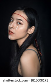 Ho Chi Minh City, Vietnam - April 25, 2020: Portrait of a girl looking straight at the camera with a white facial pattern and red hairspring in the studio.