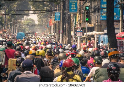 HO CHI MINH CITY, VIETNAM - FEBRUARY 2, 2013: traffic jam with a congestion of scooters and people with colorful helmets. There are approximately 340,000 cars and 3,5 million motorcycles in the city.