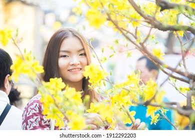Ho Chi Minh city, Vietnam - January 25, 2020: Young girl with blooming ochna flowers in Vietnamese Tet holiday