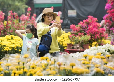 Ho Chi Minh city, Vietnam - Jan 2021: People visit the flower market to find and buy for themselves beautiful flower pots to decorate their homes on Lunar new year.