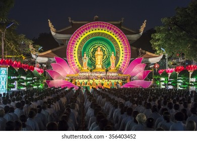 Ho Chi Minh City, Vietnam - December 27th, 2015: Buddhists toward stage night  Buddha Amitabha with flower beds shine, shimmer  statues monks sitting meditation  strictly in Ho Chi Minh city, Vietnam