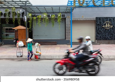 HO CHI MINH CITY, VIETNAM - NOVEMBER 24: Street food vendor in traditional conical hat on November 24, 2015 in Ho Chi Minh City, Vietnam.