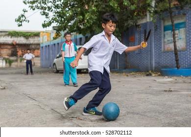 HO CHI MINH CITY, VIETNAM - October 31, 2016: Vietnamese boys playing football in front of school building in Ho Chi Minh City, Vietnam.