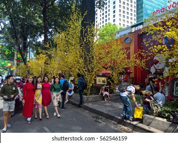 Ho Chi Minh city, Vietnam - Jan 22, 2016: : Atmosphere of springtime with colorful scene on Saigon street, Vietnamese woman in ao dai, posing beside flower to take photo on Tet holiday