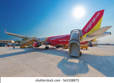 HO CHI MINH city, VIETNAM - MARCH 18, 2016: A Vietjet Air plane having arrived from Bangkok stands empty in the airfield ready for next flight. VietJet Air is a young low coster in Vietnam.