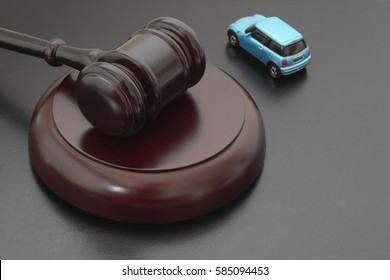 HO CHI MINH CITY, VIETNAM - FEBRUARY 19, 2017: Judge gavel and toy car on black board. Symbol of law, justice and auction.