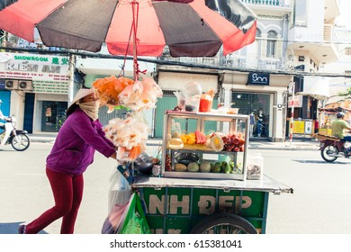 Ho Chi Minh City, Vietnam - March 29, 2014: Vietnamese woman in conical hat sells fruits on the street of Saigon on March 29, 2014 in Ho Chi Minh City, Vietnam.