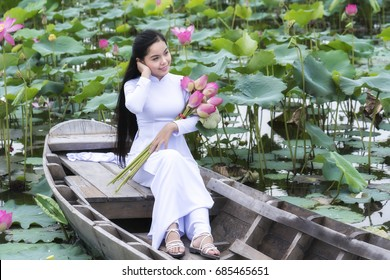 Ho Chi Minh City, Vietnam - July 16th, 2017: Vietnamese girl in traditional long dress or Ao Dai inside boat floating in lotus pond is coy as to maintain their youth time in Ho Chi Minh City, Vietnam