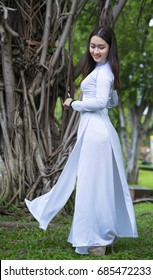 Ho Chi Minh City, Vietnam - July 23rd, 2017: Vietnamese girl in traditional long dress or Ao Dai posturing under the old banyan youth express also timeless in Ho Chi Minh City, Vietnam