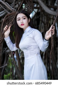 Ho Chi Minh City, Vietnam - July 23rd, 2017: Vietnamese girl in traditional long dress with eyes fascinated wait for a loved one in emotional gorgeous forever with time in Ho Chi Minh City, Vietnam